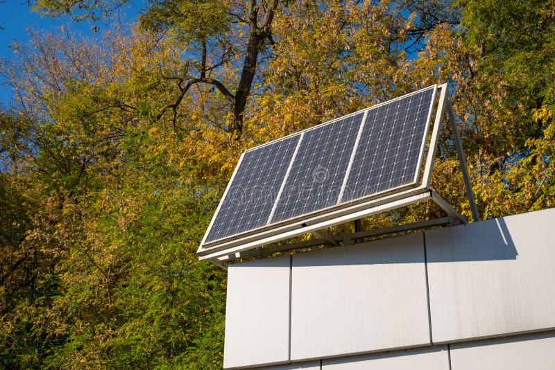 Plan rapproché d'un toit de construction avec un panneau solaire sur le dessus, sur un fond de ciel bleu et d'automne photographie stock