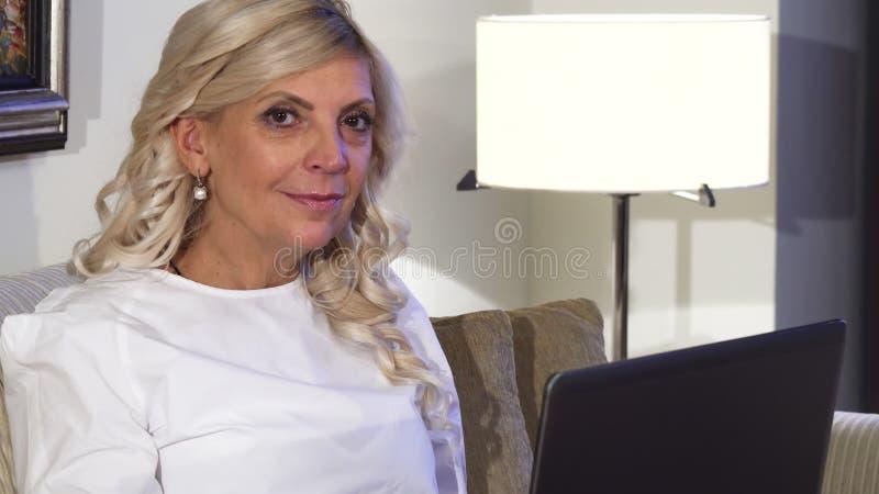 Plan rapproché d'un visage du ` s de femme qui fonctionne derrière son ordinateur portable photos libres de droits