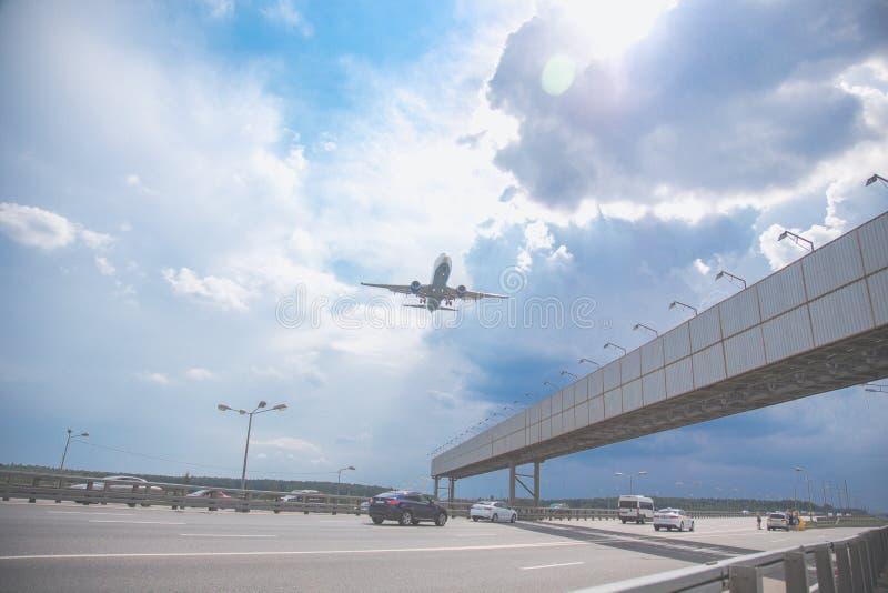 Plan rapproché d'un vol d'avion de passagers au-dessus d'une route contre un ciel bleu photos libres de droits