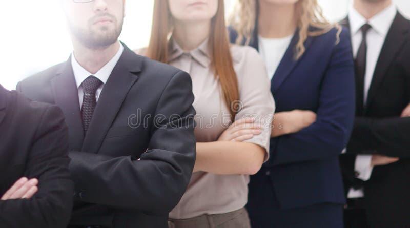 Plan rapproché d'une équipe d'affaires souriant côte à côte et croisant leurs bras images libres de droits