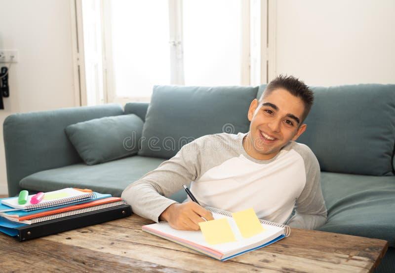 Plan rapproché d'une étude heureuse et gaie de jeune homme, fonctionnant dans le travail Étude des livres à la maison images stock