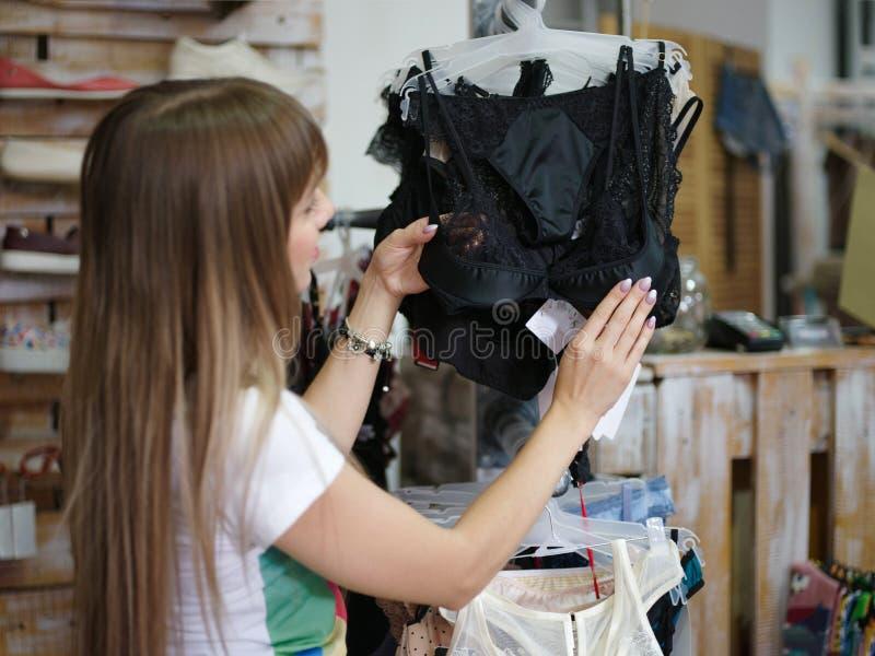 Plan rapproché d'une belle femme se tenant dans le magasin d'habillement et se choisissant sous-vêtements sexy Un shopaholic sur  photo stock