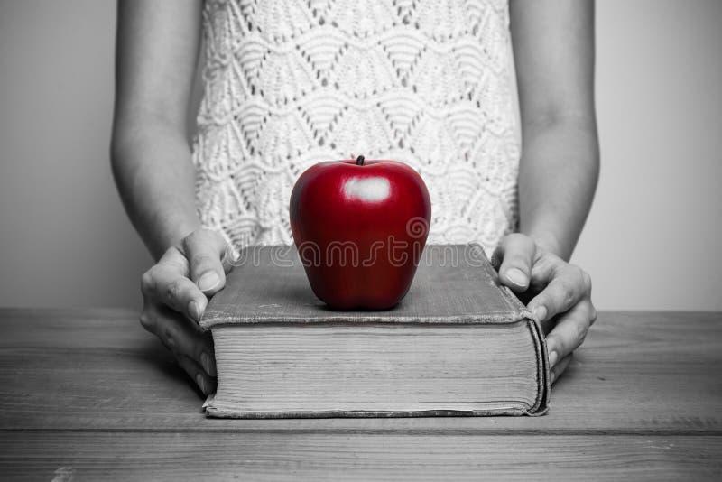Plan rapproché d'une femme chrétienne lisant la bible avec la pomme rouge photographie stock libre de droits