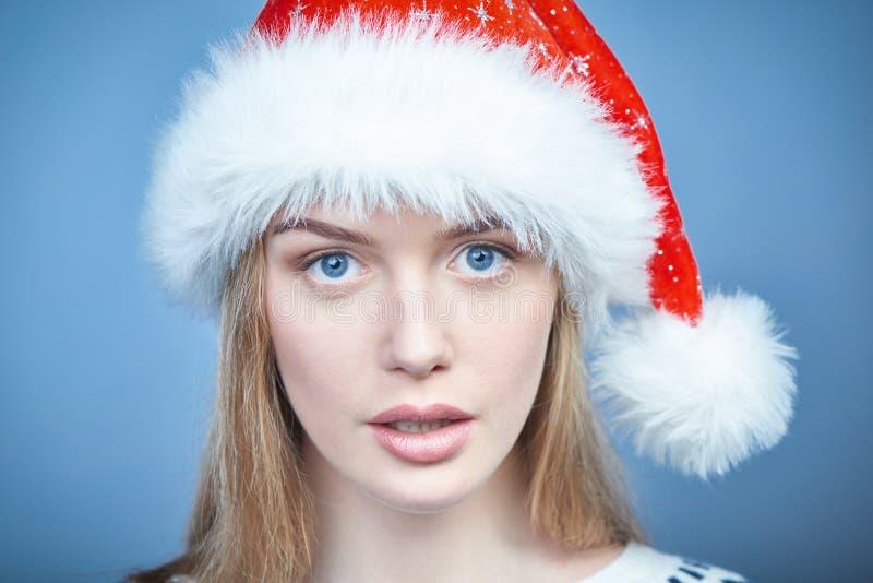 Plan rapproché d'une femme utilisant le chapeau de Santa, regardant la caméra image stock