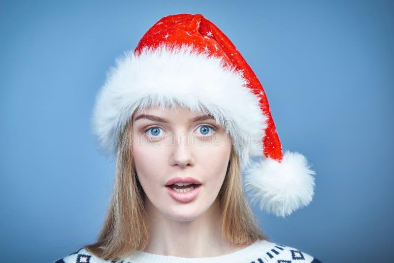 Plan rapproché d'une femme utilisant le chapeau de Santa, regardant la caméra photos libres de droits