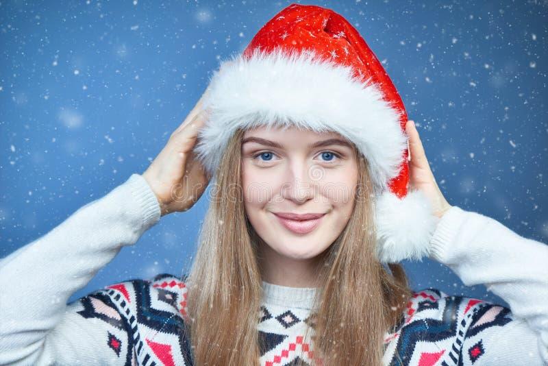Plan rapproché d'une femme utilisant le chapeau de Santa, regardant la caméra photo stock