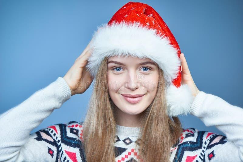 Plan rapproché d'une femme utilisant le chapeau de Santa, regardant la caméra images stock