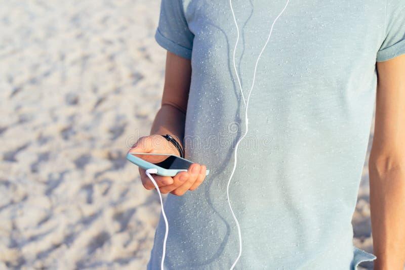 Plan rapproché d'une fille dans un T-shirt bleu tenant un téléphone portable dans h photographie stock