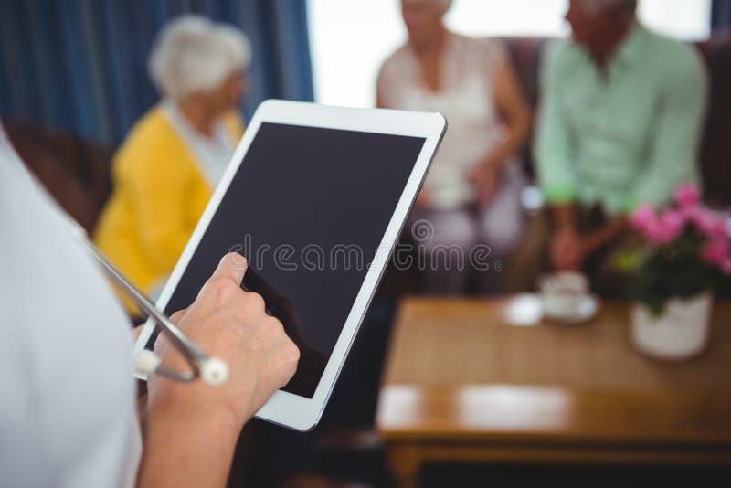 Plan rapproché d'une infirmière tenant un comprimé numérique photos stock