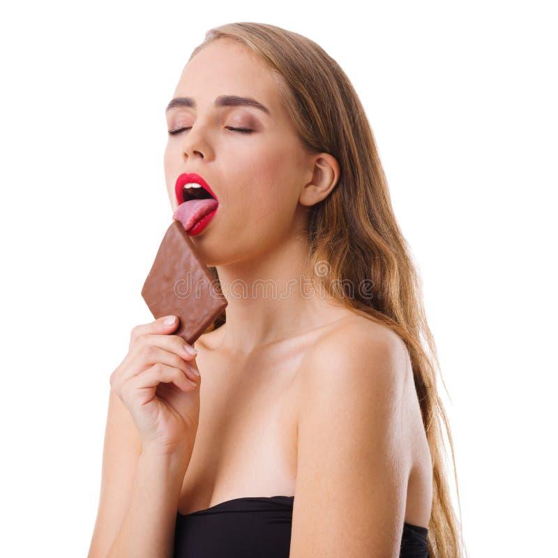 Plan rapproché d'une jeune fille, blonde, avec un morceau de chocolat dans des ses mains d'isolement sur le fond blanc photos stock
