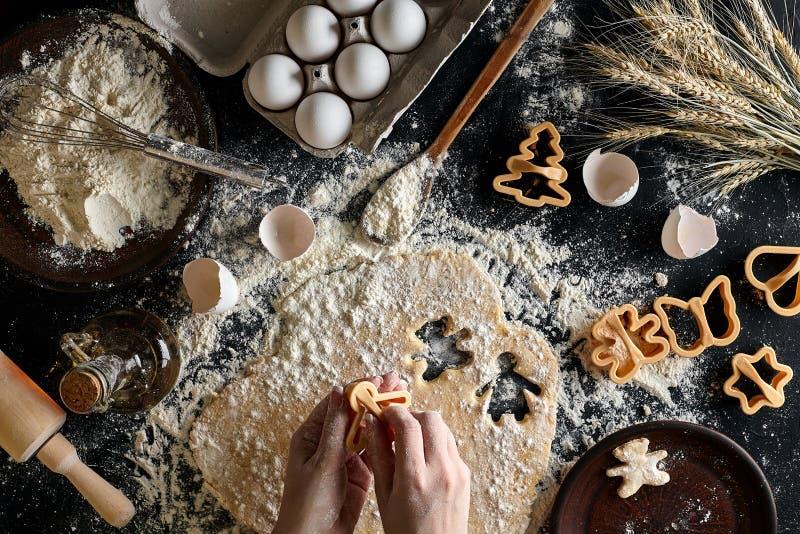 Plan rapproché d'une main du ` s de femme avec une pâte La femme coupe un biscuit avec un coupeur de biscuit sous forme de image libre de droits