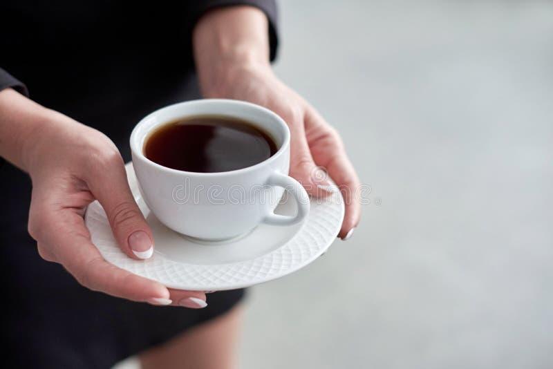 Plan rapproché d'une main du ` s de femme tenant une tasse de café chaud dans le bureau image libre de droits