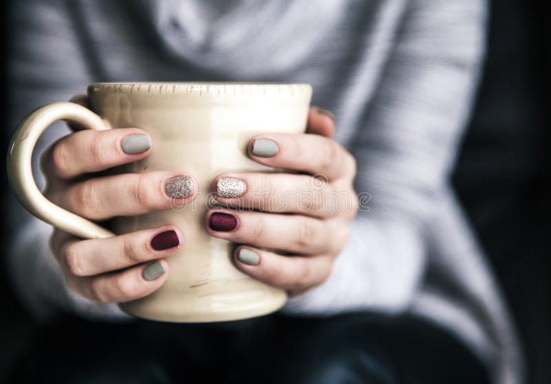 Plan rapproché d'une main du ` s de femme tenant une tasse de café chaud mode, loisirs images libres de droits