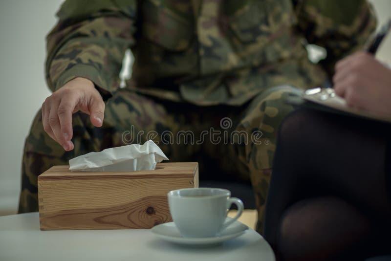 Plan rapproché d'une main du ` s de soldat prenant un tissu d'une boîte pendant la thérapie image stock