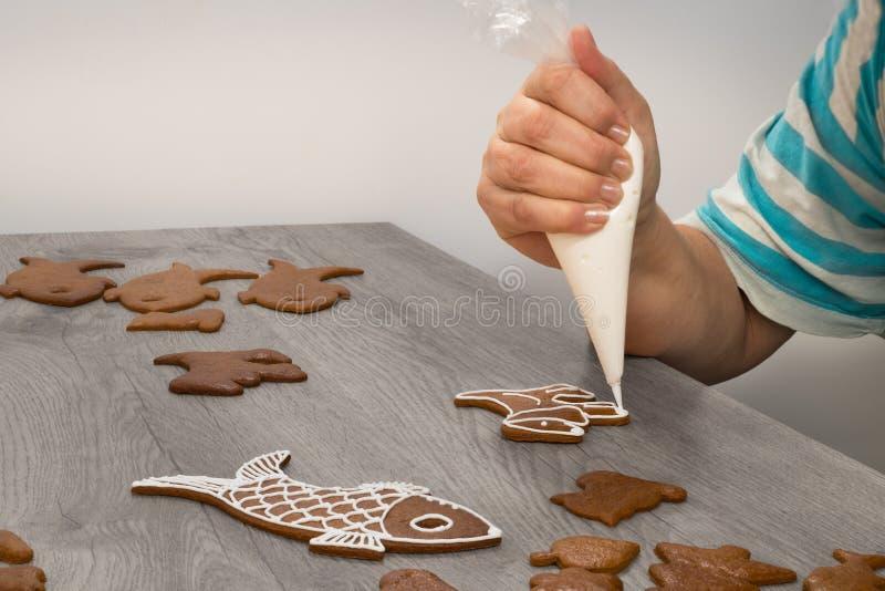Plan rapproché d'une main femelle en décorant des pains d'épice de Noël images libres de droits