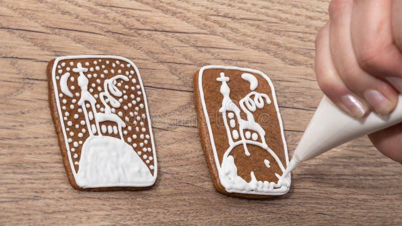 Plan rapproché d'une main femelle tout en décorant le pain d'épice de Noël sur une table en bois image libre de droits