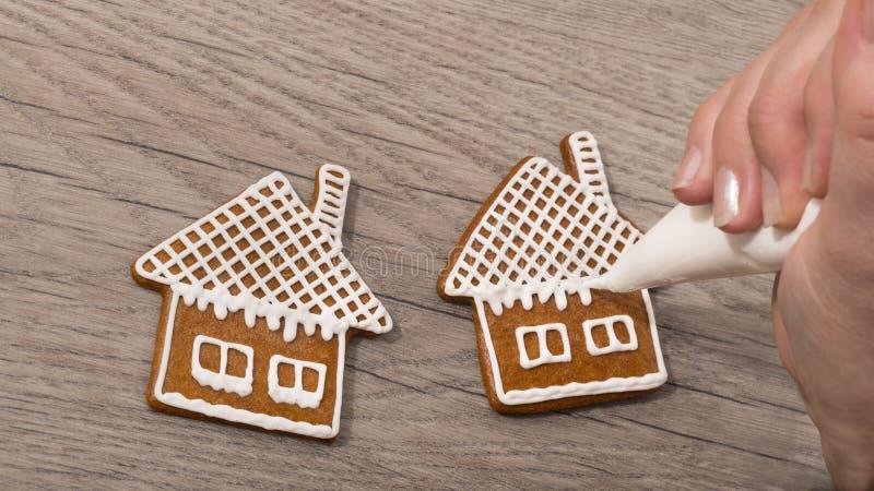 Plan rapproché d'une main femelle tout en décorant les pains d'épice doux sur une table en bois images libres de droits