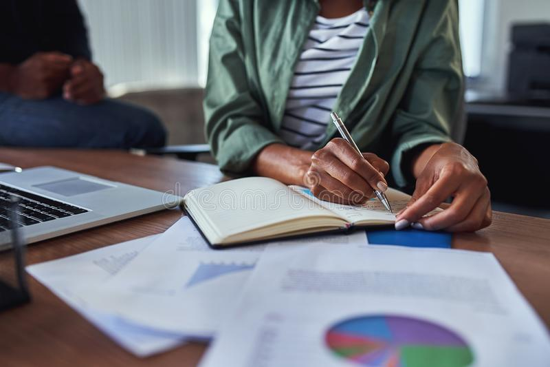 Plan rapproché d'une note d'écriture de femme d'affaires en journal intime sur le bureau images libres de droits