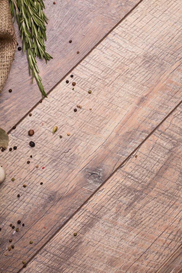 Plan rapproché d'une table en bois légère avec différents assaisonnements parfumés et brindilles de romarin vert sur un fond en b images stock