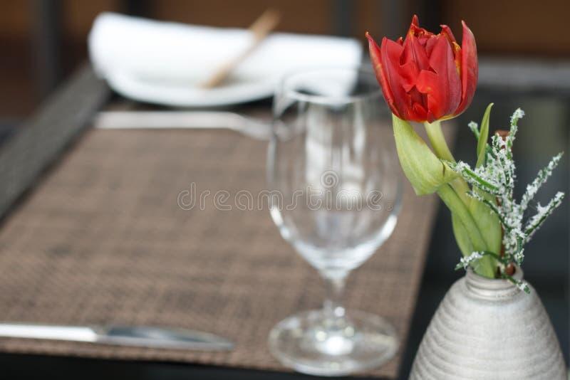Plan rapproch? d'une tulipe rouge dans un petit vase au-dessus de la table avec un verre de vin dans un caf? ou un restaurant photo libre de droits
