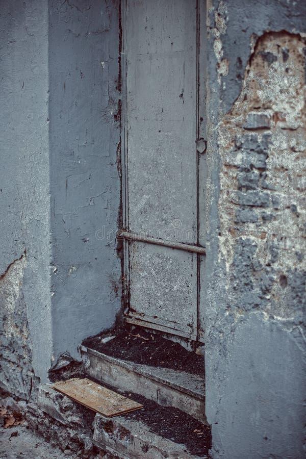 Plan rapproché d'une vieille porte rouillée dans un secteur suburbain de la ville avec les murs moitié-détruits photo libre de droits