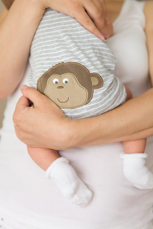 Plan rapproché de bébé minuscule dans les chaussettes dans les mains de sa mère Jeune maman étreignant son enfant nouveau-né Mate images stock