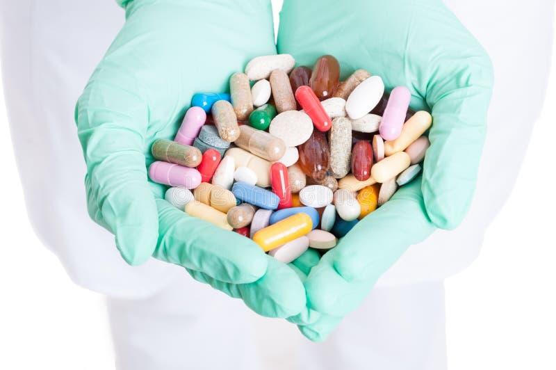 Plan rapproché de beaucoup de pilules, de capsules et de comprimés dans des mains de docteur photos stock