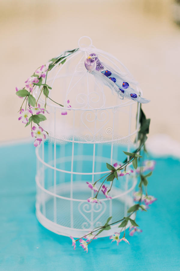 Plan rapproché de belle cage à oiseaux décorative avec quelques fleurs mignonnes d'isolement sur la table couverte par la nappe d images stock