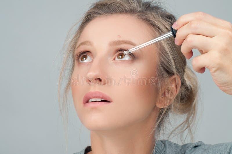 Plan rapproché de belle femme appliquant Eyedrops dans ses yeux photographie stock