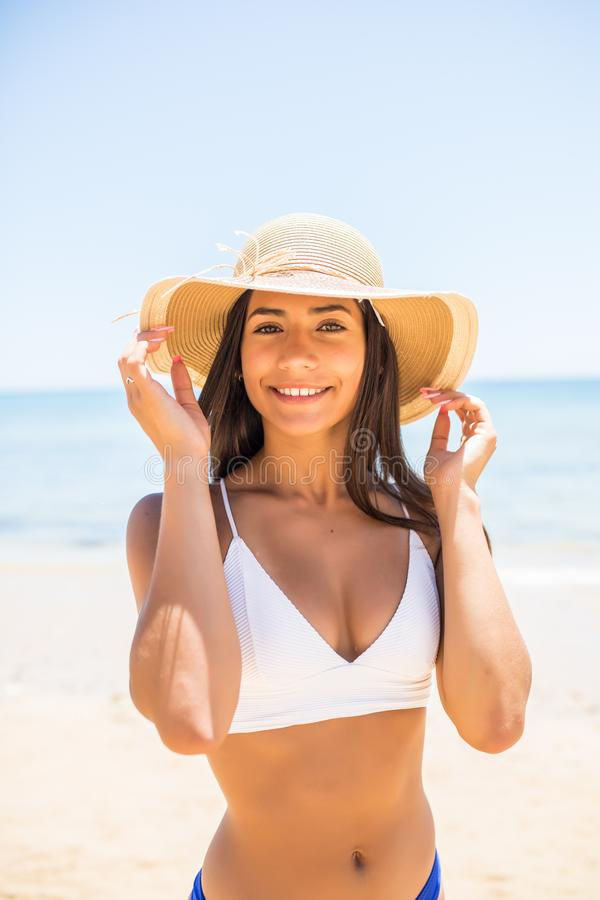 Plan rapproché de belle jeune femme de sourire à la plage avec Straw Hat sur la plage de mer photos stock