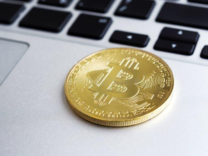Plan rapproché de Bitcoin d'or sur l'ordinateur portable images stock