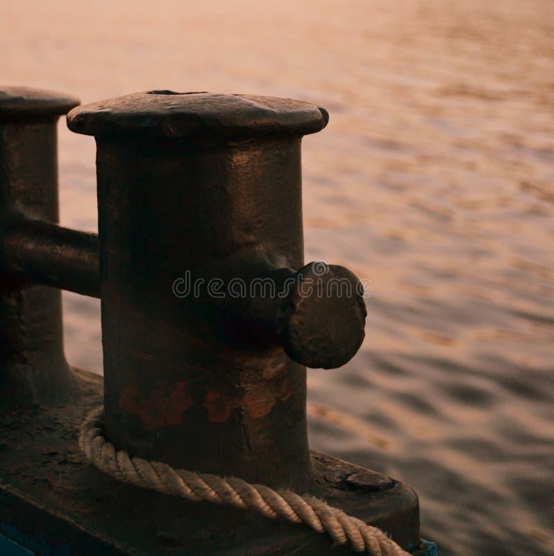 Plan rapproché de borne sur le pilier avec un morceau de corde photographie stock