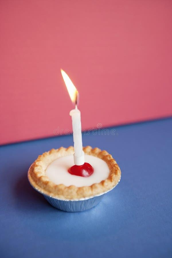 Plan rapproché de bougie brûlant sur le petit gâteau au-dessus du fond coloré image stock