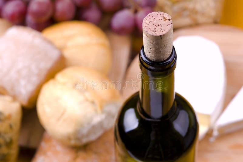 Plan rapproché de bouteille de vin avec la nourriture traditionnelle photo stock