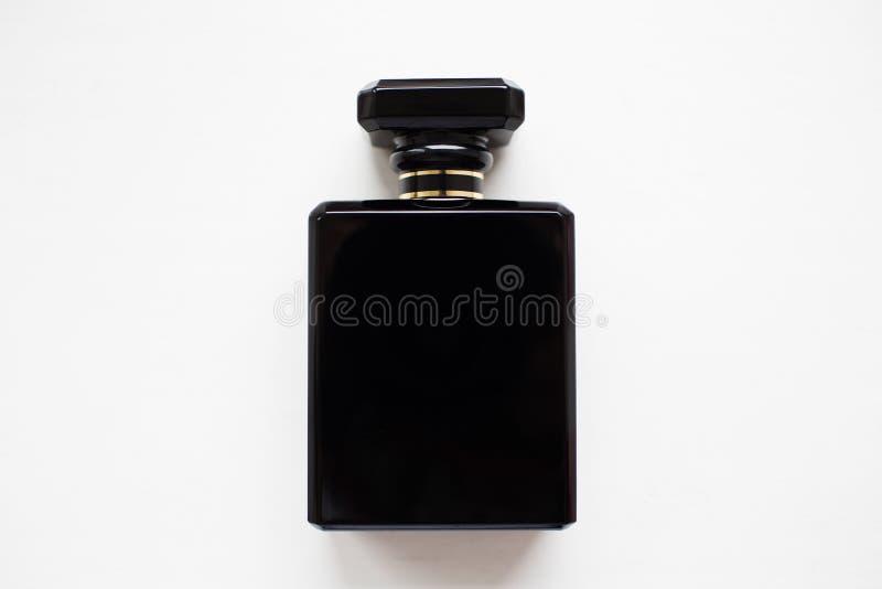 Plan rapproché de bouteille de parfum noire, d'isolement sur le blanc photographie stock