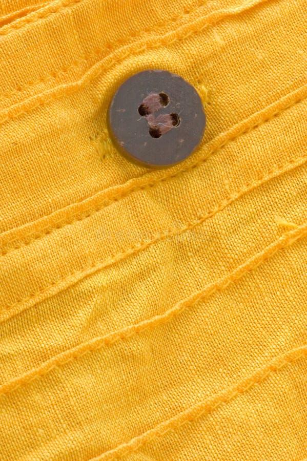 Plan rapproché de bouton en bois sur le coton organique jaune photographie stock libre de droits