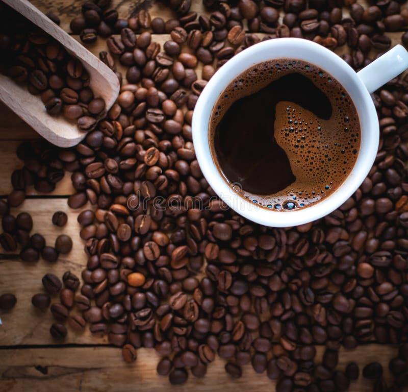 Plan rapproché de café noir dans la tasse blanche, avec des grains de café sur le fond en bois photos stock