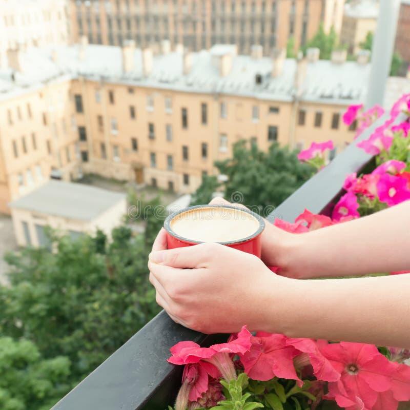 Plan rapproché de café potable de jeune femme sur le balcon image stock