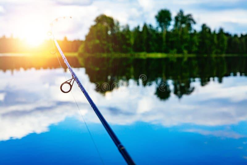 Plan rapproché de canne à pêche avec un beau lever de soleil sur le lac bleu en Finlande image libre de droits