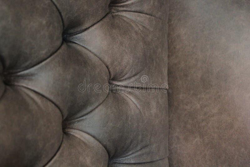 Plan rapproché de chaise élégante de Chesterfield Pr?sidence en cuir bourr?e Seat et dos avec des boutons avec l'espace libre pou photo libre de droits