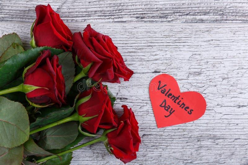 Plan rapproché de cinq roses rouges sur un fond gris, avec un coeur de papier, jour du ` s de St Valentine images libres de droits