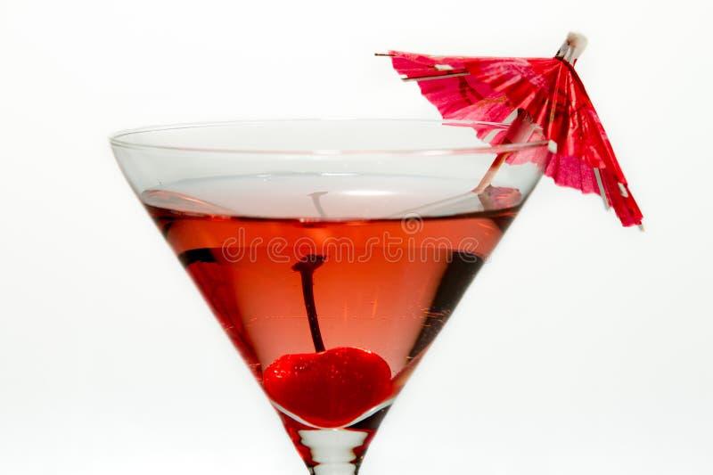 Plan rapproché de cocktail rouge de martini avec un parapluie photographie stock libre de droits