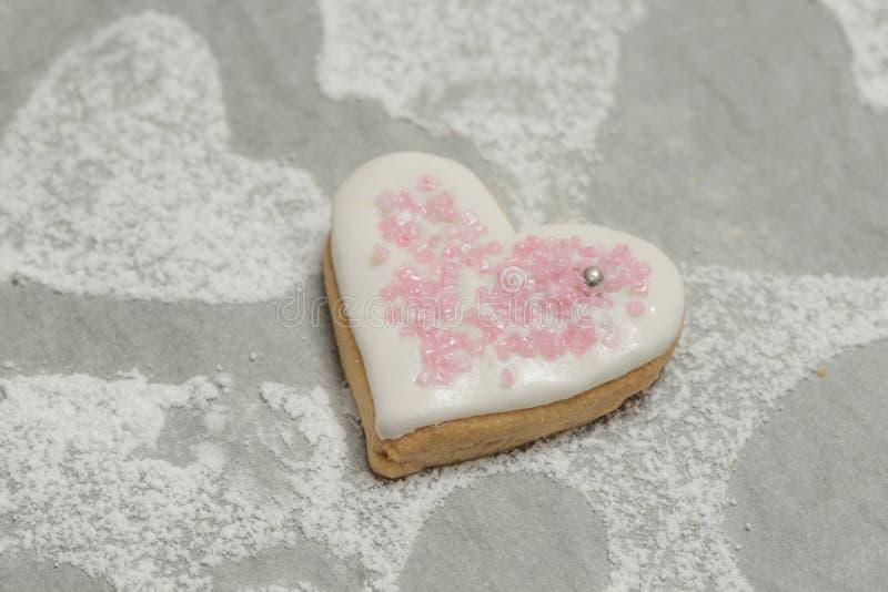 Plan rapproché de coeur cuit au four avec le glaçage blanc et le décor rose photographie stock