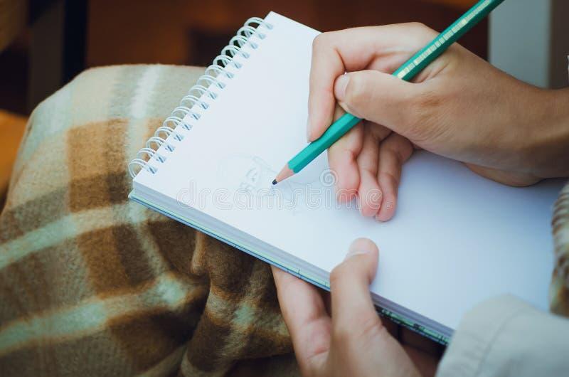 Plan rapproché de crayon et du dessin de participation de main dans le carnet illustration libre de droits