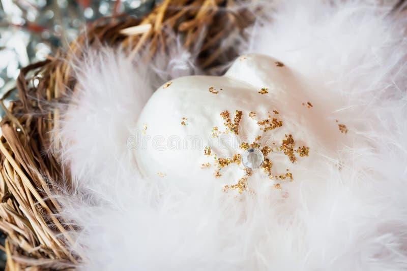 Plan rapproché de décoration de Noël des mitaines décoratives blanches de celluloïde avec les plumes d'oiseau pelucheuses dans le image libre de droits