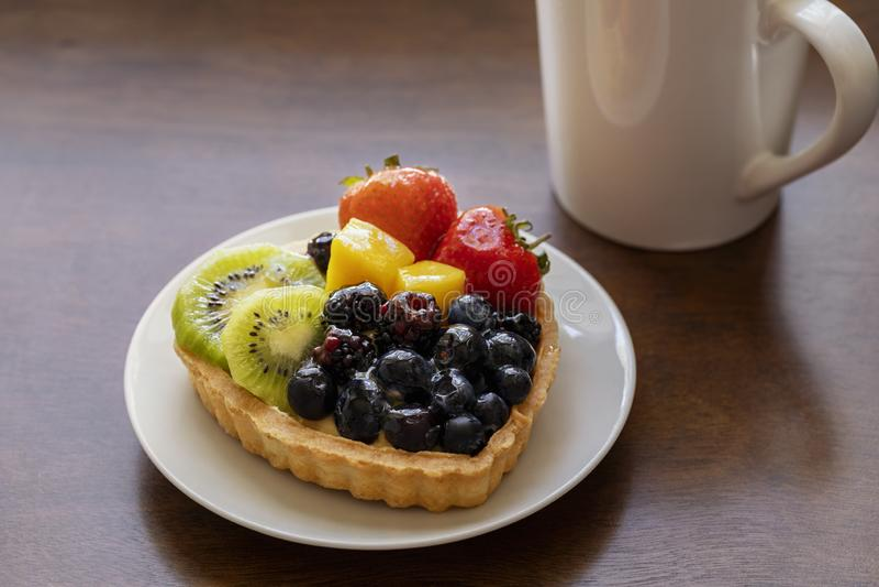 Plan rapproché de dessert au goût âpre de fruit avec les fraises, le kiwi, la crème de fromage et le café noir chaud photo stock