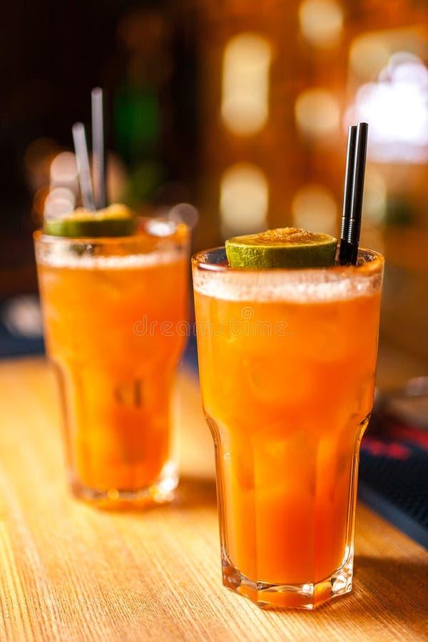 Plan rapproché de deux cocktails oranges colorés avec la chaux et le sucre roux dans la barre image stock