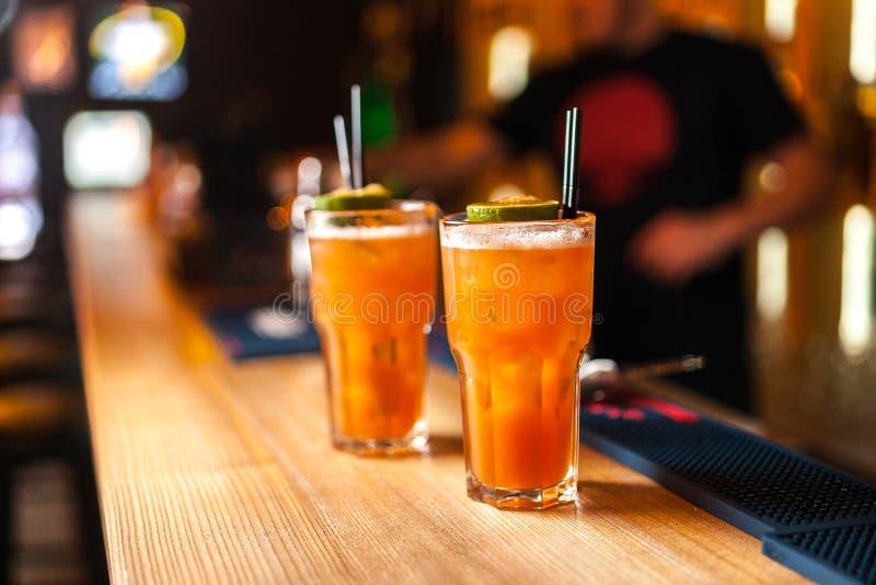 Plan rapproché de deux cocktails oranges colorés avec la chaux et le sucre roux dans la barre, fond brouillé images stock