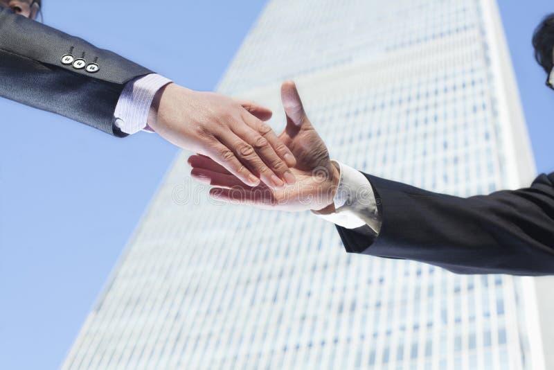 Plan rapproché de deux gens d'affaires se serrant la main par le World Trade Center dans Pékin, Chine photos libres de droits