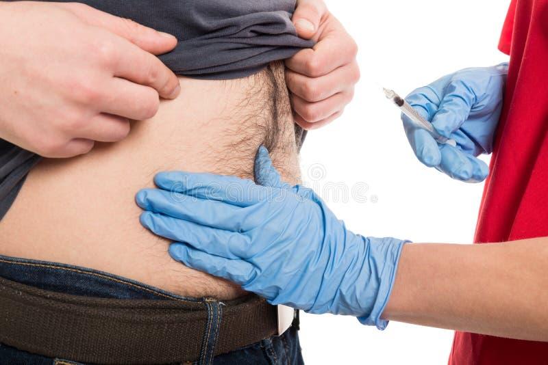Plan rapproché de docteur féminin donnant l'injection au ventre patient masculin image libre de droits